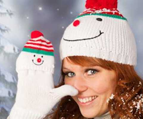 Portrait of woman in winter with snow and snowman hat